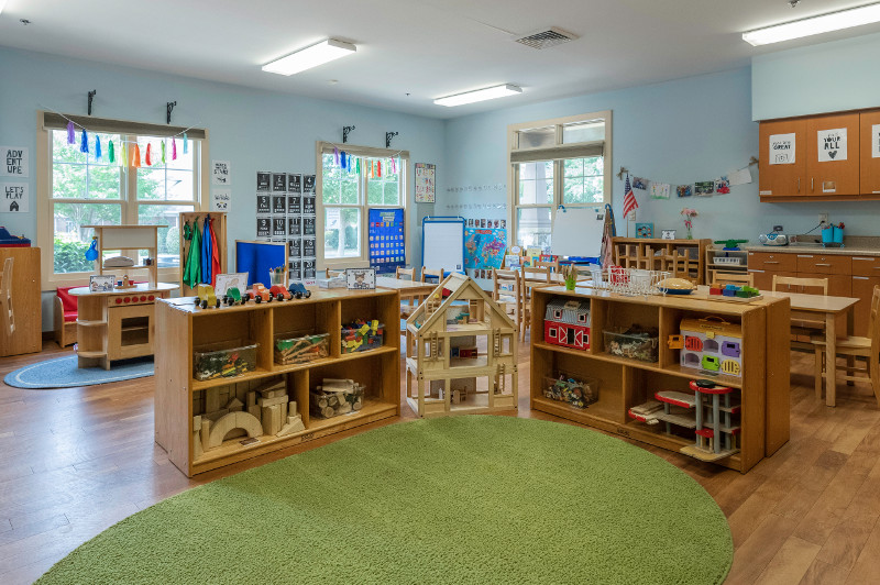 Brightly lit kindergarten classroom with toys and book neatly arranged